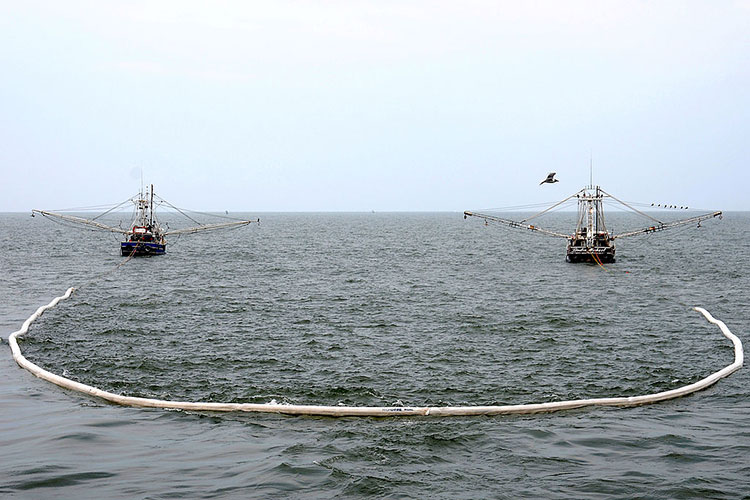 Shrimp boats tow fire-resistant oil-containment boom in Gulf of Mexico